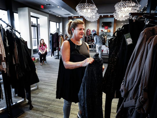 Kaufman Shoes employee Stacy Siegler, places clothes