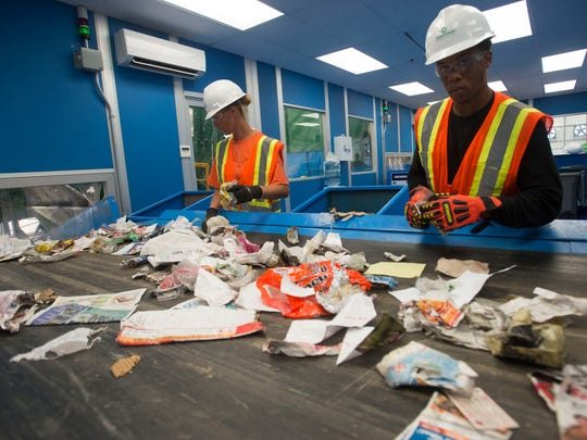 ECUA recycling center workers, April Derry, left, and Jerry Foster, right, look for non-recyclable materials on the sorting lines at the Beulah Landfill sorting facility. Much of the non-recyclable items include organic material, plastic bags, and medical waste.