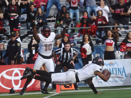 UNLV's Armani Rogers (1) scores a touchdown while taking on Nevada during the battle for the Fremont Cannon football game at Mackay Stadium in Reno on Nov. 25, 2017.