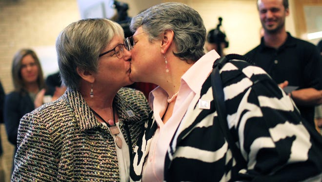 Alexis Leonard, left, and Chelsea Beresford kiss before applying for a marriage license at the Buncombe County Register of Deeds office in Asheville, N.C., Oct. 15, 2013.