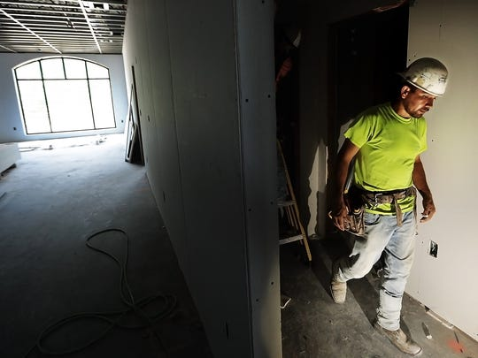 Jorge Loa works on the drywall in apartments at the