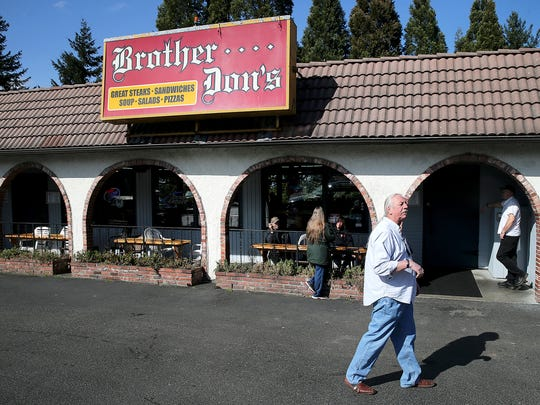 Gordon Rinke, manager of Brother Don's on Kitsap Way in Bremerton, walks in front of the bar Tuesday.