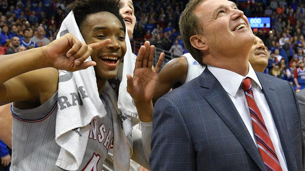 "Dec 6, 2016; Lawrence, KS, USA; Kansas Jayhawks guard Devonte' Graham (4) signals ""six"" while head coach Bill Self watches congratulatory messages from former players on his 600th win. Kansas Jayhawks beat the UMKC Kangaroos 105-62 at Allen Fieldhouse.  Mandatory Credit: Denny Medley-USA TODAY Sports ORG XMIT: USATSI-330392 ORIG FILE ID:  20161206_lbm_sm8_269.JPG"