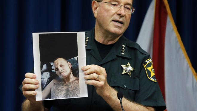 "Sheriff Grady Judd holds a photograph of Tony ""T.J."" Wiggins, the alleged shooter in the Lake Streety Road triple homicide, during Wednesday's media briefing."