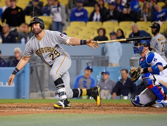 Pittsburgh Pirates' Francisco Cervelli drops his bat after a two-run home run, in front of Los Angeles Dodgers catcher Yasmani Grandal during the ninth inning of a baseball game, Wednesday, May 10, 2017, in Los Angeles. The Dodgers won 5-2. (AP Photo/Mark J. Terrill)