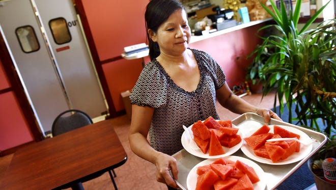 Quynh Danh serves watermelon to customers at Pho Quynh on Thursday. Customer traffic at the restaurant has slowed since the 12th Street bridge project started.