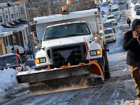 A plow truck from the City of Wilmington clears snow along Washington St.  from this past weekends massive storm on Monday morning