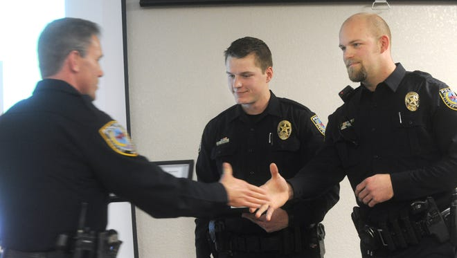 Police Chief Stan Standridge, left, presents a Medal of Valor to officers Jerod Daniel, center, and Cory Davis, right, for pulling a woman out of a burning house in October.