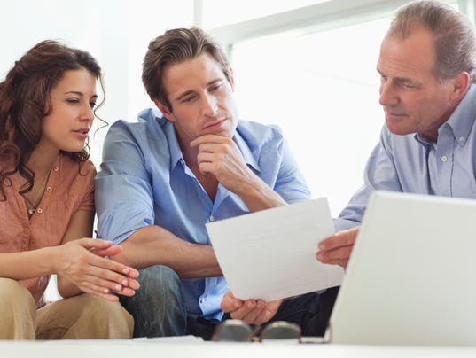 Couple going over paperwork with financial advisor