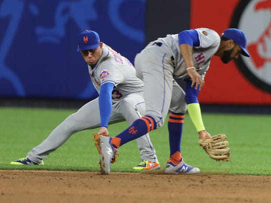 Mets shortstop Amed Rosario cuts in front of second baseman Asdrubal Cabrera to make a play in the ninth inning and the Mets went on to beat the Yankees, 7-5, in Yankee Stadium on Friday, July 20, 2018.