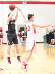 Sacred Heart's Cullen Hughes (1) shoots over USJ's Harrison Homberg (3) on Tuesday.