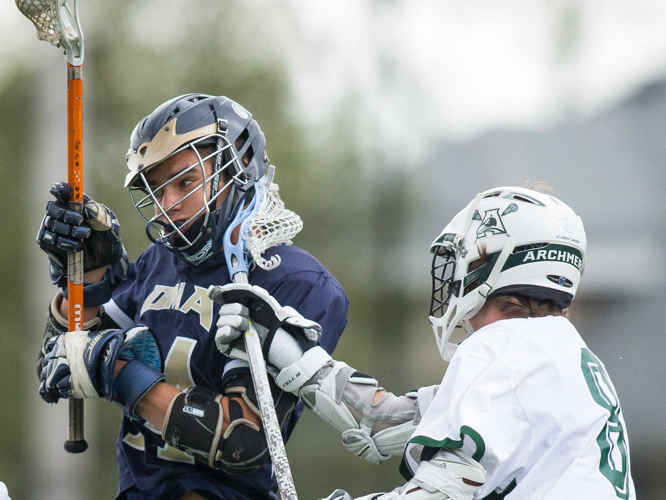 DMA's John Szczecinski (left) gets a stick to the side of his head from Caleb Smack of Archmere.
