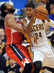 Indiana Pacers forward Paul George backs Washington Wizards forward Nene into the lane inside Bankers Life Fieldhouse, Friday, January 10, 2014, in Indianapolis.