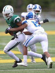 West Bloomfield's AJ Abott is tackled by Walled Lake Western's Abdur-Rahmaan Yaseen during the second half of Western's 19-14 win over West Bloomfield on Thursday, Aug. 24, 2017, at Comerica Park.