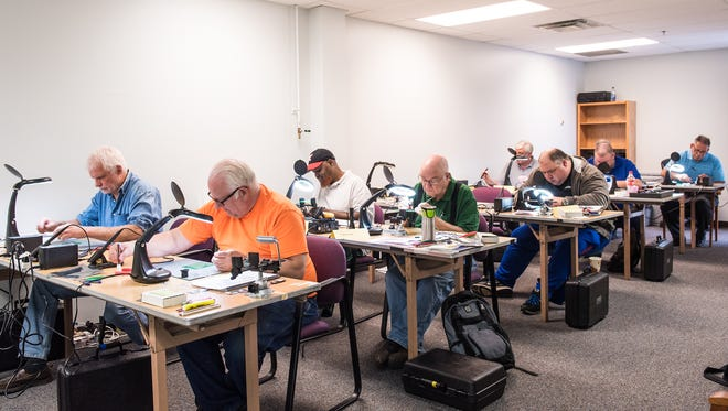 Students work on making circuit boards as part of the Veterans and Displaced Workers in Manufacturing program at Rochester Institute of Technology.