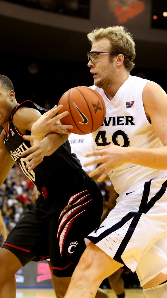 Cincinnati guard Troy Caupain battles for the loose ball against Xavier center Matt Stainbrook in December of 2013.