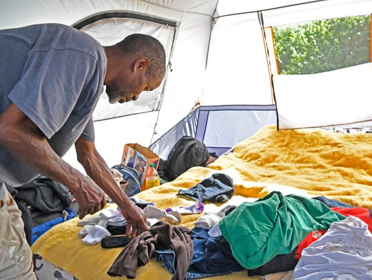 Kenneth Tharpe folds clothes inside his tent. Tharpe