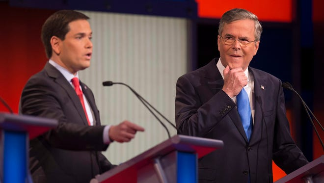 Marco Rubio speaks as Jeb Bush looks on during the Republican debate on Jan. 28, 2016, in Des Moines.