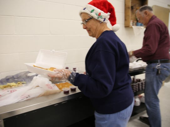 Deane Lamb prepares a box of food to be delivered Monday,