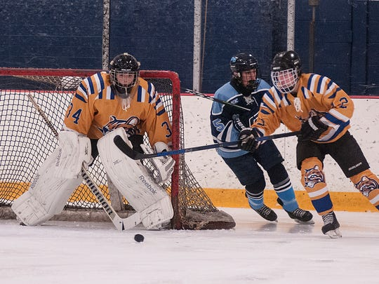 Schoolcraft goalie Bryan Donaldson watches as teammate Zach Nichols (No. 12) fends off Northwood's Aaron Owen.