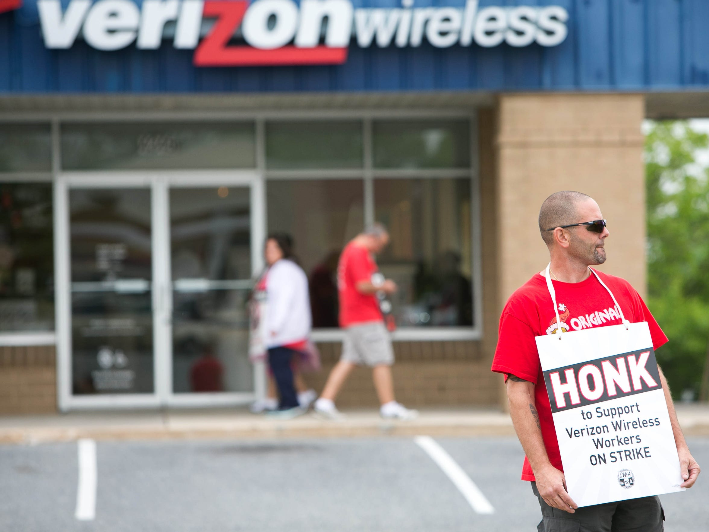 """Carrying a sign that reads """"Honk to support Verizon Wirless workers on strike"""", John Inzaina, a Verizon employee for 25 years, pickets at the Verizon store on Kirkwood Highway in Wilmington."""