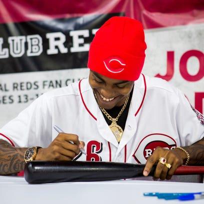 Raisel Iglesias, Reds pitcher, autographs a fan's bat
