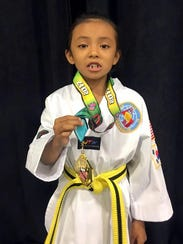 Dallas Kanesewah shows her gold medal.