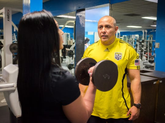 Fitness trainer Johnny Jimenez coaches client Stefanie Hernandez on the use of free weights at Las Cruces Fitness Center.  Varying the workouts helps clients maintain interest, he said.