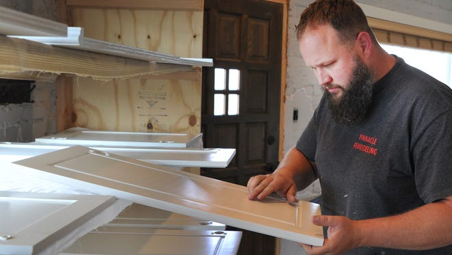 Chad Staelens, co-owner of Pinnacle Remodeling located at the corner of Scott Avenue at 4th Street looks at some cabinet doors in his business showroom Thursday morning. Chad and his wife, Nicole,  located their business there in 2011.