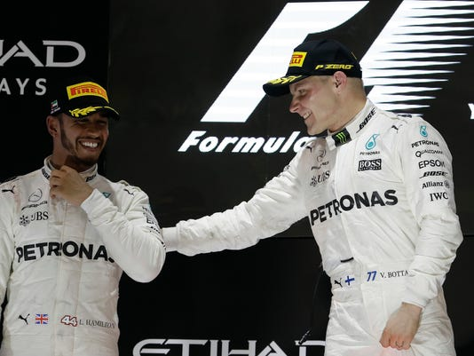 FILE - In this Sunday, Nov. 26, 2017 file photo, Mercedes driver Lewis Hamilton of Britain, left, and Mercedes driver Valtteri Bottas of Finland celebrate after the Emirates Formula One Grand Prix at the Yas Marina racetrack in Abu Dhabi, United Arab Emirates.  Valtteri Bottas has no intention of playing second fiddle to Lewis Hamilton and is aiming to pip his Mercedes teammate to the title. Bottas joined Hamilton at Mercedes at the start of 2017 to replaced Nico Rosberg, following the shock retirement of the then world champion. (AP Photo/Luca Bruno, file)