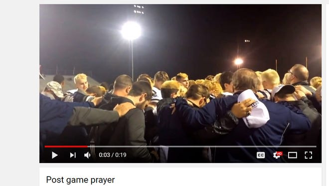 A screenshot of a YouTube video showing Reitz coach Andy Hape leading student athletes in prayer after a game in October 2014.