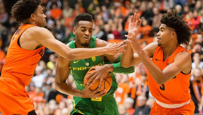 Jan 5, 2018; Corvallis, OR, USA; Oregon Ducks forward Troy Brown (0) drives between Oregon State Beavers guard Stephen Thompson Jr. (1) and guard Ethan Thompson (5) during the first half during a game at Gill Coliseum. Mandatory Credit: Troy Wayrynen-USA TODAY Sports
