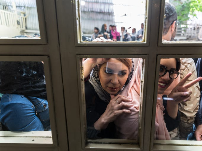 Voters in Tehran wait to cast their ballots in the