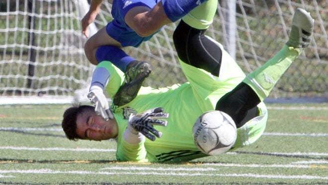 Goshen's Eryk Piasecki tumbles over Valhalla goalkeeper Lorenzo Luciano as Luciano makes the save during the Section 1 vs. Section 9 boys soccer challenge at Mamaroneck High School Oct. 10, 2016. Goshen defeated Valhalla 1-0 in overtime.