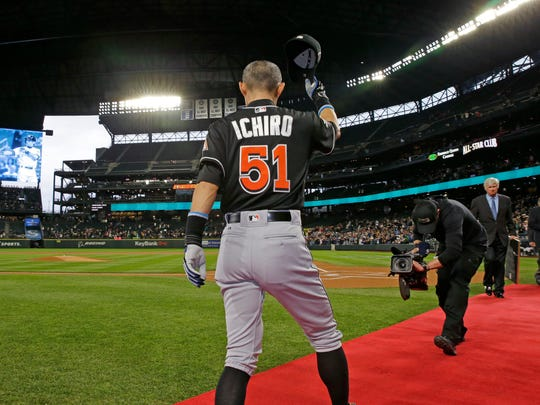 The Miami Marlins' Ichiro Suzuki tips his cap after