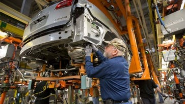Greg Middleton, a GM employee for 28 years, assembles a 2015 Buick Enclave on April 30, 2015 at the GM Lansing Delta Township Assembly plant.