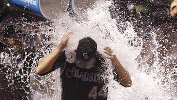 Colorado Rockies starting pitcher Tyler Anderson is doused by teammates Jason Motte, back left, and Brandon Barnes after a baseball game against the Philadelphia Phillies, Saturday, July 9, 2016, in Denver. Anderson had his first career win in the big leagues.