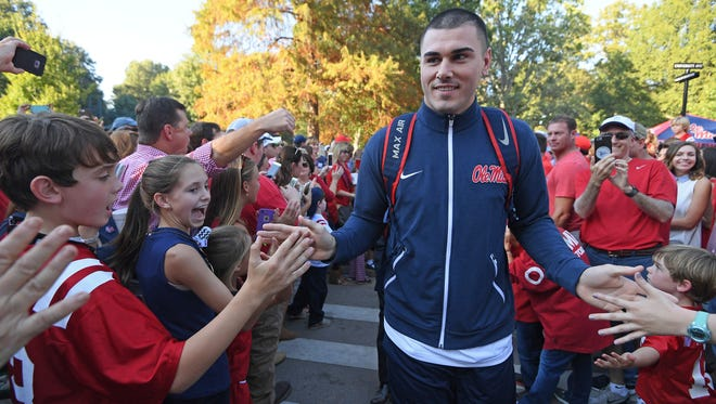 Mississippi's Chad Kelly greets fans during the Walk of Champions before an NCAA college football game between Mississippi and Auburn in Oxford, Miss., Saturday, Oct. 29, 2016. (AP Photo/Thomas Graning)