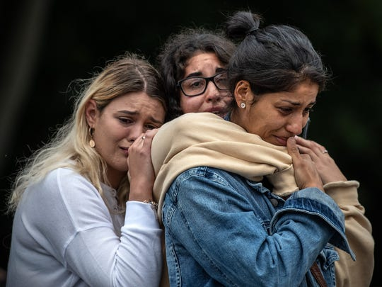 Young women weep as they hold each other for comfort during a students vigil near Al Noor mosque on March 18, 2019 in Christchurch, New Zealand.