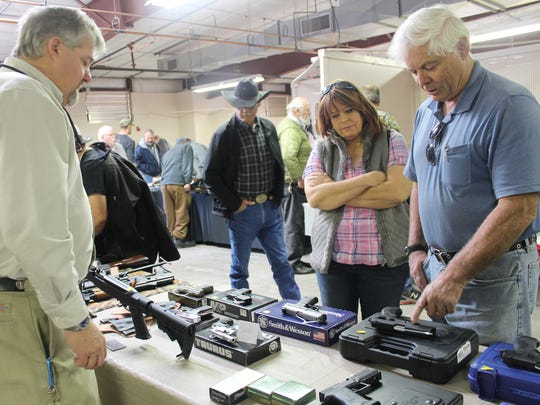 Community members browse guns from Four Points Armory during Saturday's show.