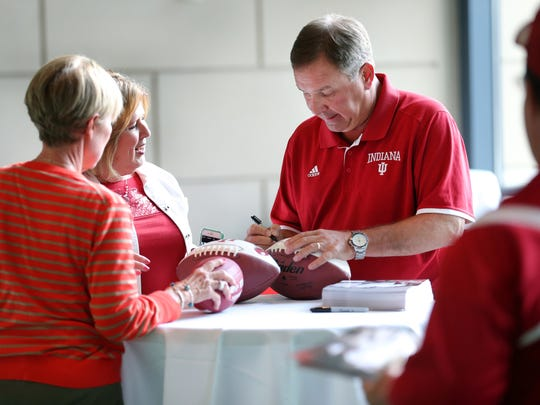 """Kevin Wilson signs footballs for Deb St. Pierre, left, and Peggy Rutledge during the IU Booster """"On The Road"""" event held at Lucas Oil Stadium, Aug. 27, 2015."""