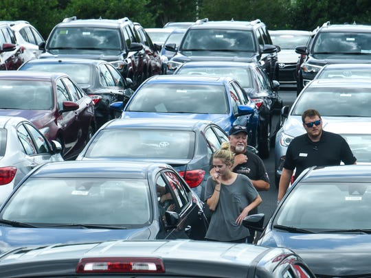 People look at new cars in the Ralph Hayes Toyota car lot in Anderson on Monday.