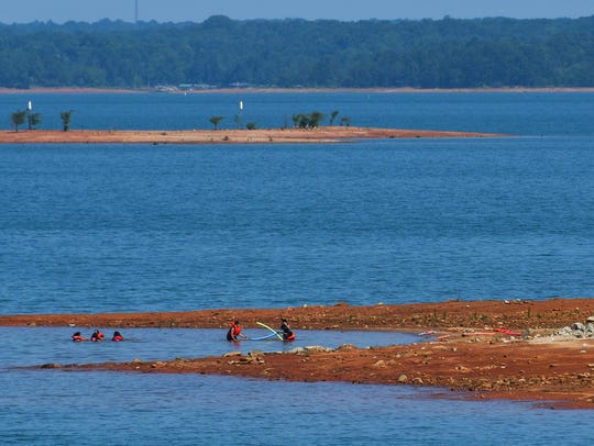 A group of swimmers play near red-clay shoreline at
