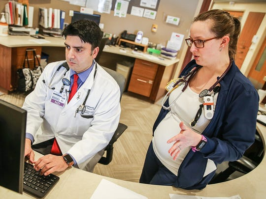 From left, Dr. Muhammad Malik and progressive care unit nurse Ashton St John discuss a patient's medical chart at Community Hospital South in Indianapolis, Friday, March 23, 2018. As a hospitalist, Malik oversees patients' care while they are hospitalized and alternates working one week on, one week off, with no call responsibilities during time off.
