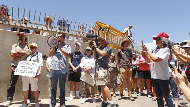 Protesters gather at the pedestrian gate of the DeConcini port of entry during the Families Belong Together march in Nogales on June 30, 2018.
