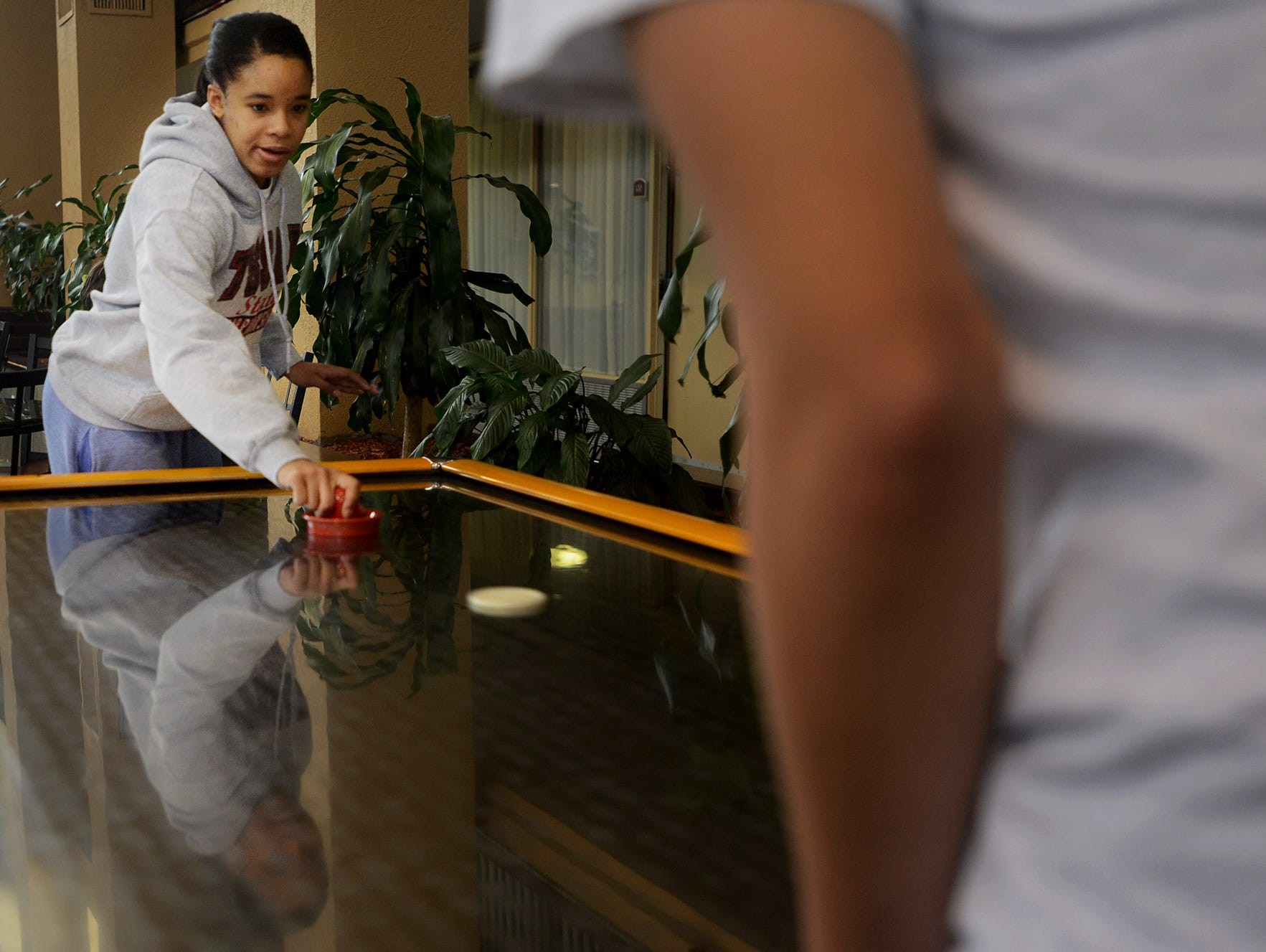 Riverside Lady Panther Deidre McElrath plays a game of air hockey with a teammate during downtime at their hotel, Thursday. The team was scheduled to play their Class AA quarterfinal game at 9:30am but will now play their game Friday at 11am.