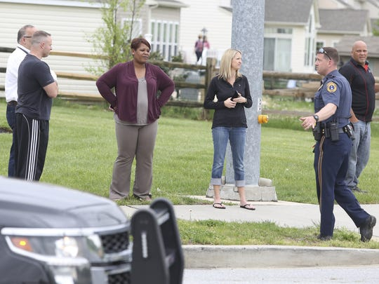 A police officer talks to people waiting to pick up students from Brick Mill Elementary School as a standoff continues nearby with a man suspected of shooting a state police officer Wednesday afternoon.