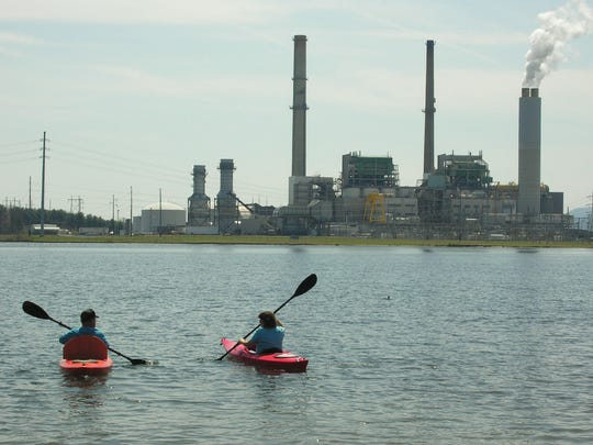 Paddlers head out onto Lake Julian across the lake from the Duke Energy plant.