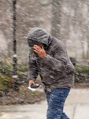 A man braces himself from heavy winds as he crosses