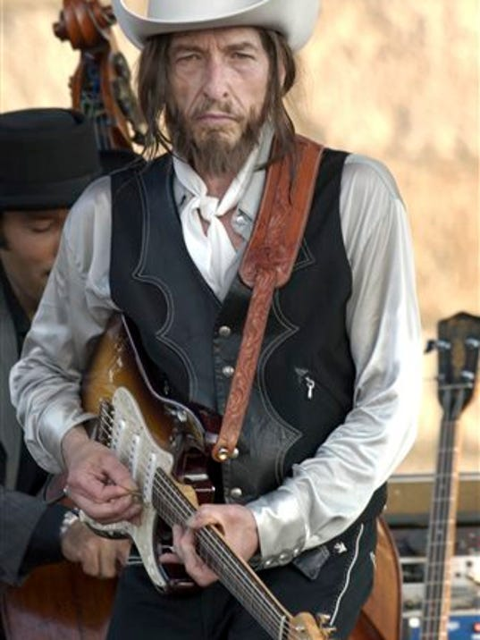 """FILE - In this Aug. 3, 2002, file photo, Bob Dylan plays an electric guitar at the Newport Folk Festival in Newport, R.I. Dylan played a Fender Stratocaster at the historic 1965 Newport Folk Festival, marking the first time he had """"gone electric"""" publicly."""